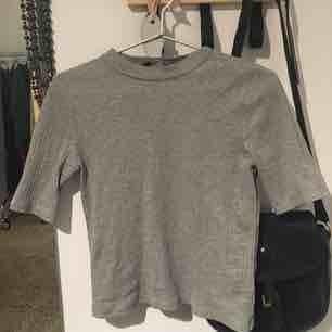 Knappt använd ljusgrå halvpolo med ribbstickning. Så fin till ett par jeans eller instoppade i vilka byxor som helst! Stretchig och mjuk.  Strl 40 men är ganska liten i storlek så passar även en 38.