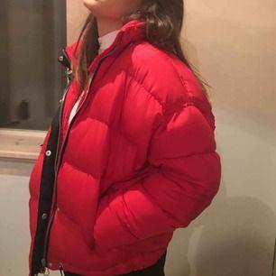 Jag har bara använt min röd puffer-jacka två gånger och tänker därmed sälja den. Jackan har knappar, dragkedja och svart insida. Den är mjuk och lite tunnare i materialet och är 55 % viskos och 45% polyester.