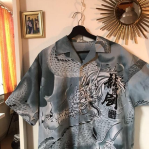 En riktigt snygg skjorta med drake och massa annat på. Köpt på beyond retro. Endast använd några gånger så väldigt bra skick. Baksidan är identisk till framsidan!