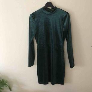 Smaragdgrön sammetsklänning från H&M. Öppen rygg och slutar ovanför knä.