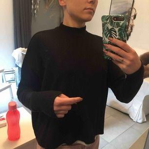 Ribbad svart halv polo tröja.