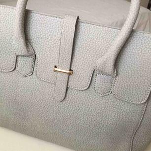 Säljer en ljusgrå handväska med många fina detaljer på. Vet ej vilket märke det är, därav det låga priset :). Helt oanvänd och ny!