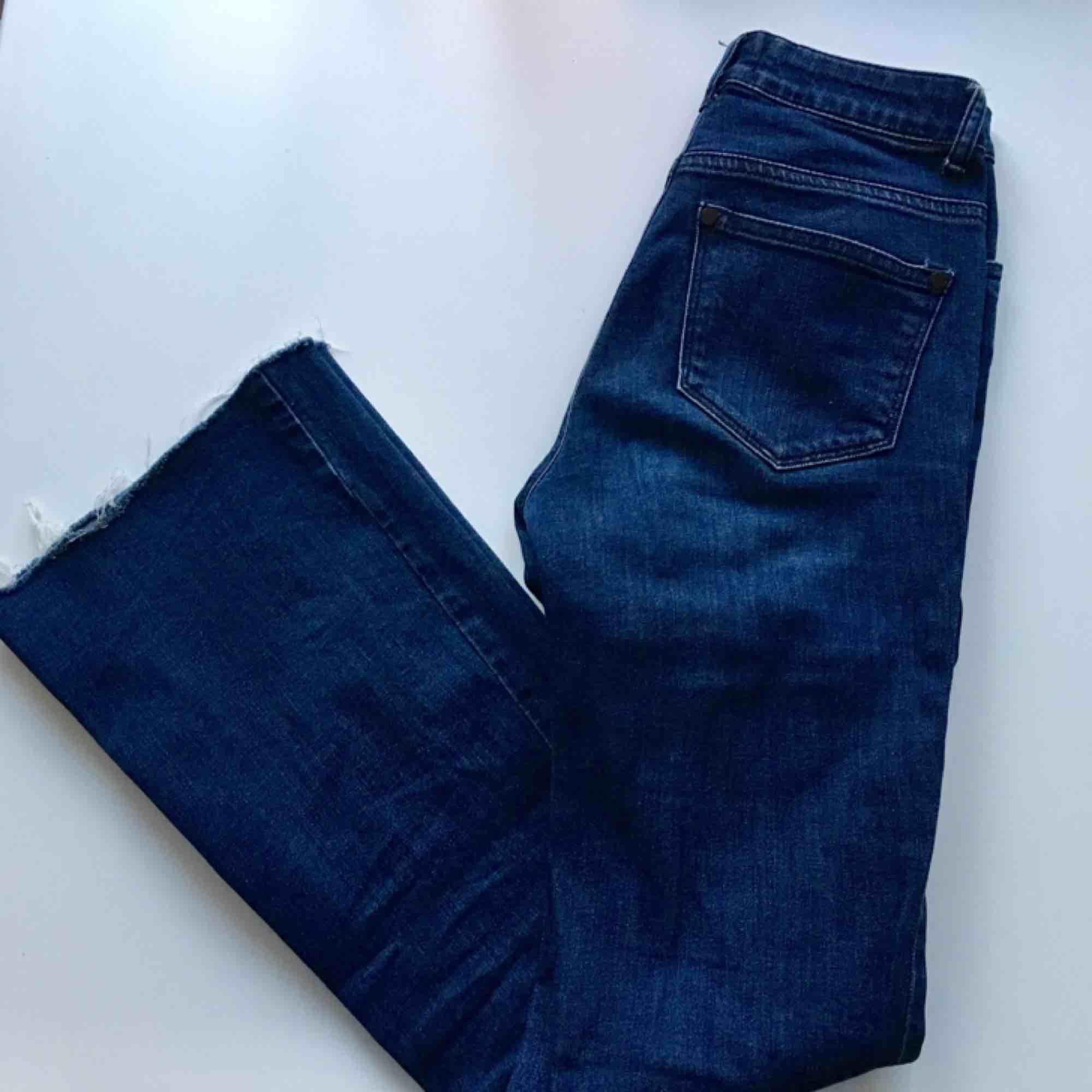 Mörkblåa jeans med bootcut, avklippta längst ner. Jeans & Byxor.