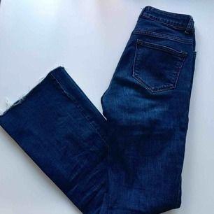 Mörkblåa jeans med bootcut, avklippta längst ner