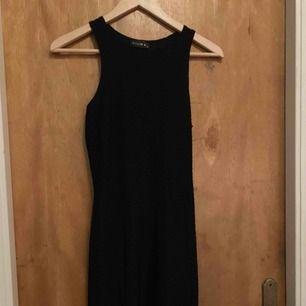Svart långklänning från club L. Två slitsar fram på klänningen.