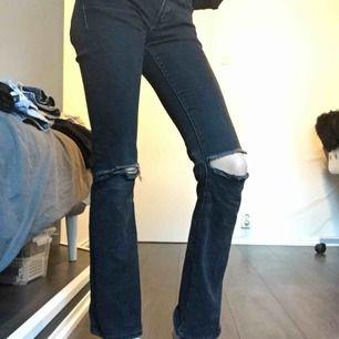 Ett par svarta bootcat jeans med hål i knäna Säljs pga för korta, köparen står för frakt