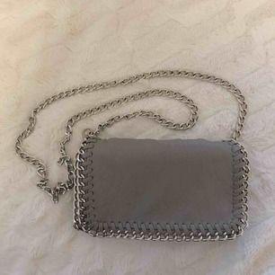 Ljusgrå Pricilla väska från Tiamo i storlek s. Har några slitningar i metallen på sidorna (se bilder), men inget som syns när väskan är på! Nypris: 450. 🌹 Frakt tillkommer!