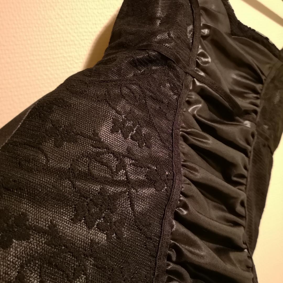 Svart linne med partier i spets på sidorna och glansigt veckat material i mitten. Justerbara axelband. Använd enstaka gång. . Toppar.