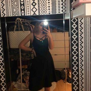 Svart fin klänning som går till knäna. Väldigt 90-tal + band som korsar över bröstet. Den är tajt till midjan och som en kjol från midjan och neråt