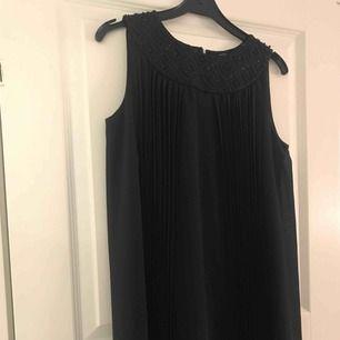 Jättefin klänning med paljetter upptill och rynkor på framsidan.