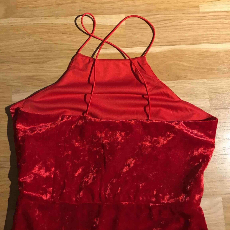 Jag säljer en röd klänning i sammet. Den kommer ifrån Nelly.com. Den är korsad i ryggen. Den är endast testad. Storlek: XS. Nypris: ca 250. Den kommer från ett djur och rökfritt hem.. Klänningar.