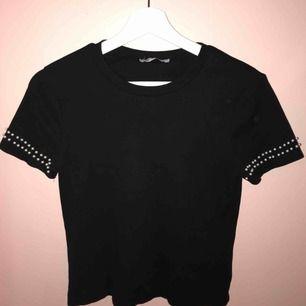 En svart basic topp från Zara med pärlor runt ärmarna. sällan använd och i fint skick. I första bilden syns en punkt som inte är en fläck utan det är en reflektion ifrån något i kameran skulle jag tro ( köparen står för frakt )