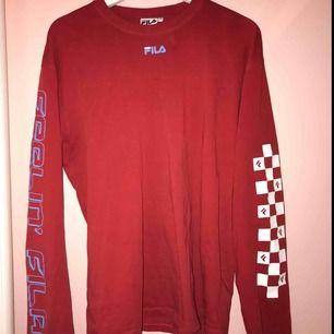 """En röd tröja från FILA x JUNKYARD med rutor på ena ärmen och texten """" feelin' fila"""" på den andra. Den är lite oversize på mig som vanligtvis har S. ( köparen står för frakt )"""