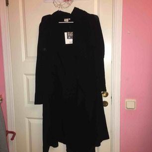 Lång kappa svart, medföljer extra knapp & svart bälte som kan knytas bak och fram