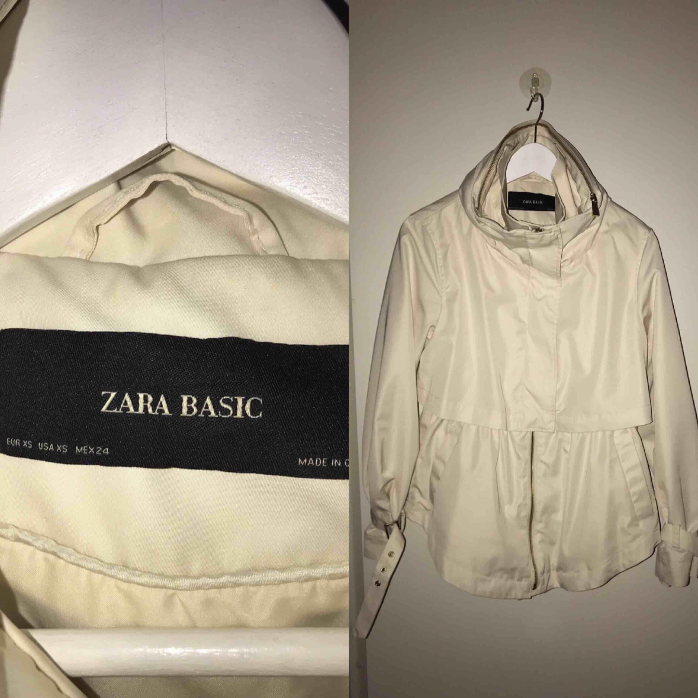 Jag säljer en beige jacka från Zara som passar utmärkt till våren! På kragen finns det en dragkedja och där finns det en luva. Storlek: XS Skick: mycket bra skick, använd max 3 gånger Nypris: 649 Kommer från ett djur och rökfritt hem. Jackor.