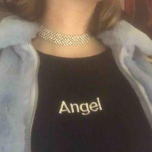 Söt topp m ordet angel på och ett par vingar på armen. Frakten ingår ej