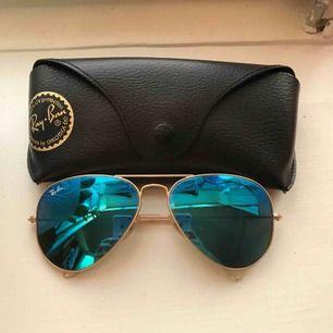Ray Ban Aviator bågar med blåfärgat glas som reflekterar en snygg spegelbild. Glasögonen är i mycket bra skick och är använda enstaka gånger. Medföljer originalfodral, putsduk och rengöringsspray. Originalpris: 1400kr