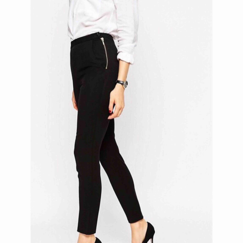 Svarta kostymbyxor med hög midja och guldig dragkedja i sidan samt på bakfickan. . Jeans & Byxor.