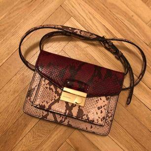 Väska i syntetläder från Mango. Rosa och rött snakeprint.  Kan mötas upp i Sthlm eller skicka. Frakten står köparen för!
