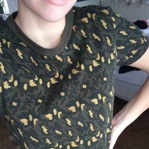 En militär mönstrad t-shirt från Weekday 🤗 Den är en aning cropped just för att det är stolek XS, men den passar mig och jag har M 👍 Säljer den svarta kjolen jag har på den andra bilden i en annan annons!