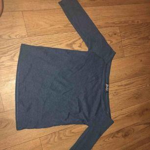En fin marinblå off shoulder tröja som är ungefär vid armvecken längd på armarna