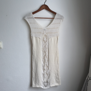 Cremevit figurnära (strand?)klänning. Den är stretchig och därför ganska flexibel i storlek. Vävd framtill där man ser igenom till huden men heltäckande baktill. Aldrig använt denna men ärvt/fått av någon för länge sen.