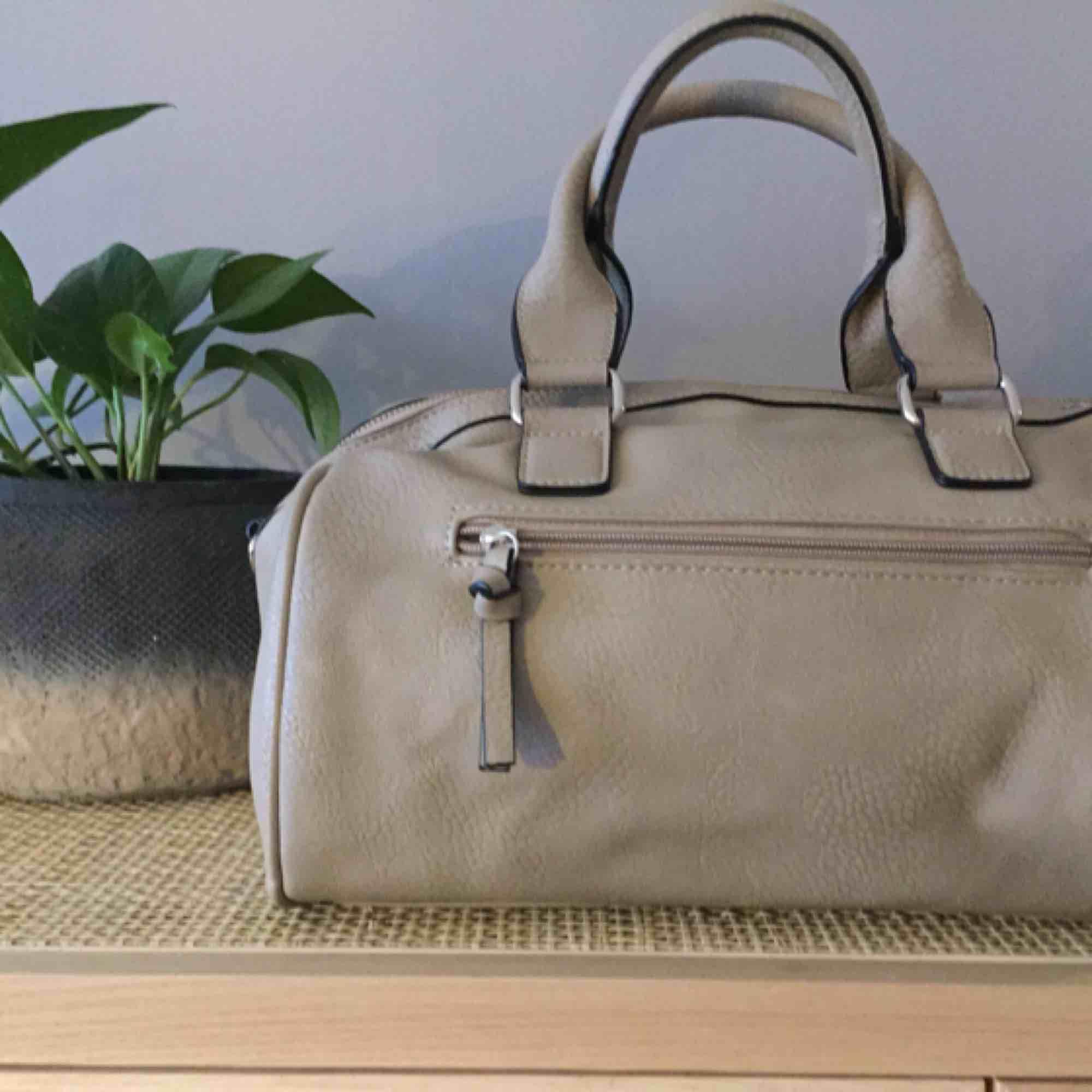 Väska i nyskick! Inget att anmärka på.  Långt band kan sättas på om man vill ha den som axelbandsväska.  . Accessoarer.