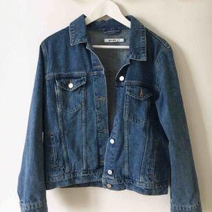 En blå jeansjacka från NA-KD i storlek 34 med ett tryck på ryggen.