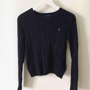 En marinblå kabelstickad tröja från Ralph Lauren i storlek 12/14yrs - som motsvarar XS ungefär.