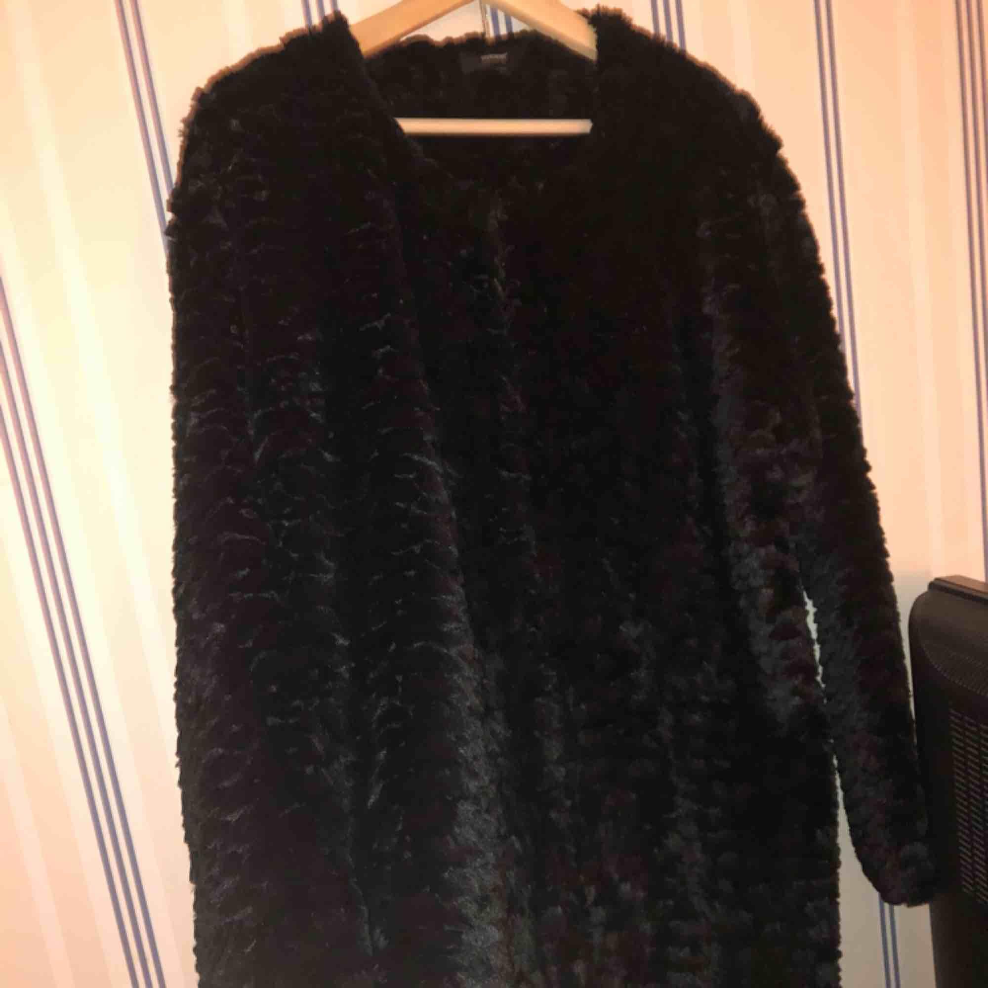 Fin svart fuskpäls jacka med hakar som knäppning. Skön och snygg nu till vår. Jackor.