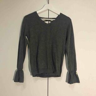 Söt tröja som endast är använd ett fåtal gånger! Snörning i ryggen och små kulor fastsydda i ärmen.