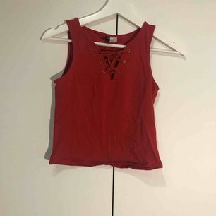 Rött linne från hm med snörning vid bröstet. Har en minimal fläck precis nedanför snörningen, dock inget som syns ifall man inte tittar noga. Kan skicka mer bilder vid intresse!  Frakt tillkommer!