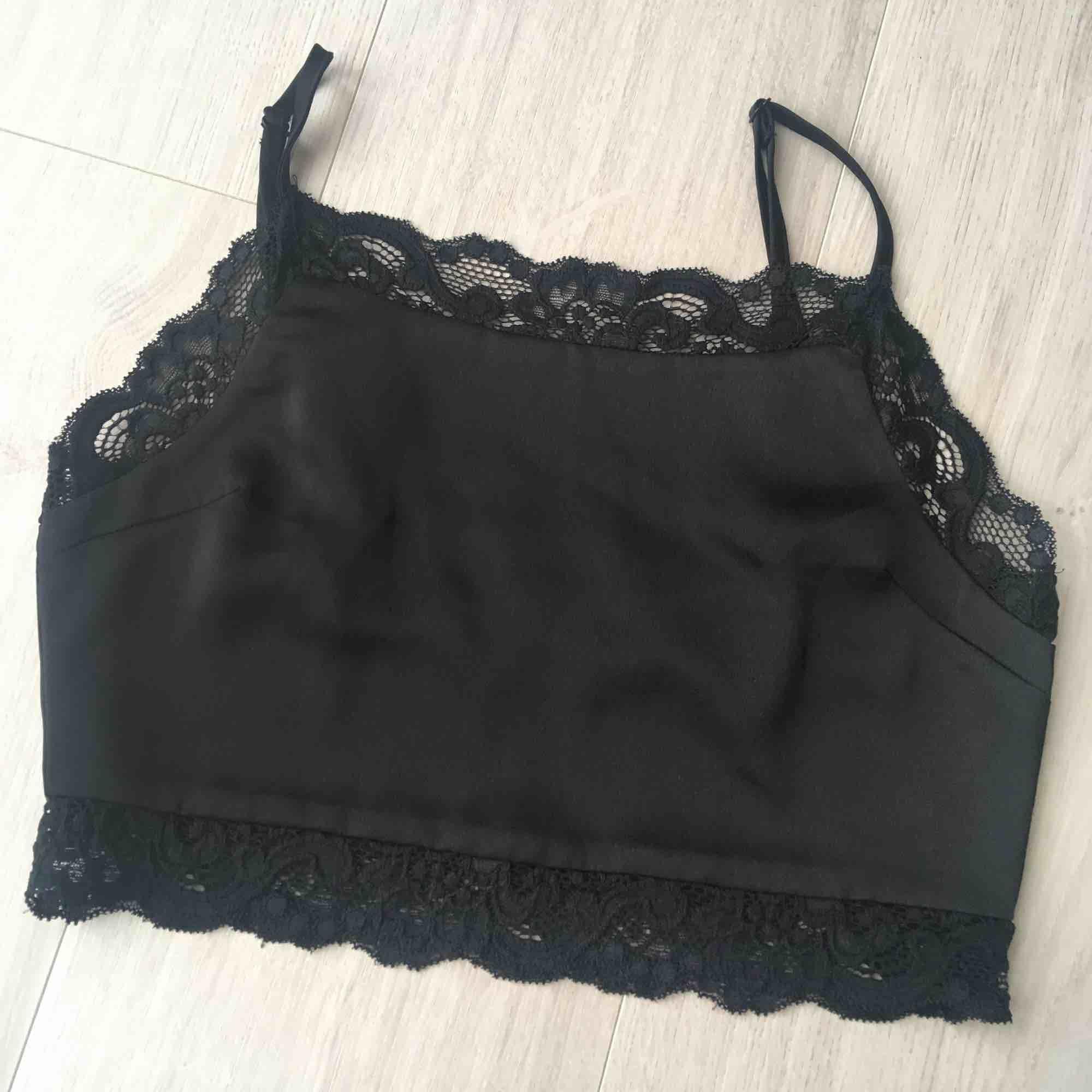 Ny svart cropped lace undertröjan från Pamela X NA-KD kollektion. Aldrig använd. Original priset är 299kr.  Frakt är plus 10kr.. Toppar.