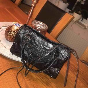 En väldigt liknade Balenziaga väska (lilla modellen) , en spegel ingår och ett längre band. ☺️