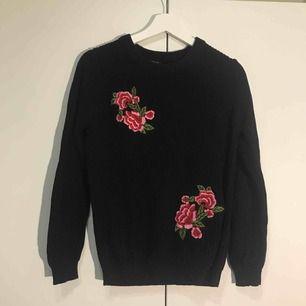En stickad marinblå tröja med fina blommor på framsidan. Sparsamt använd. Passar även en S!  Frakt tillkommer!