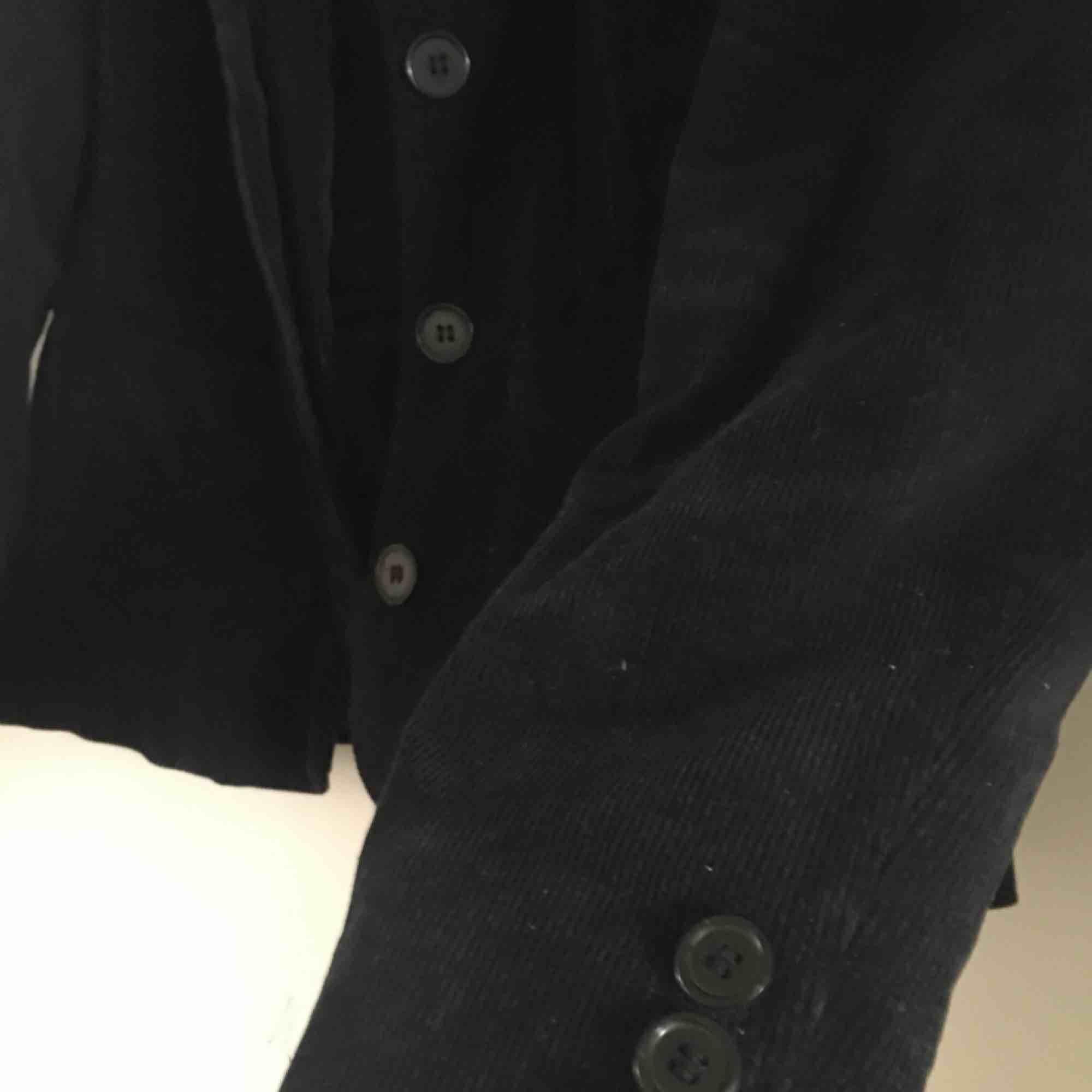 En manchesterkavaj i en marinblå färg. Står storlek 42 men skulle nog säga att den är liten i storleken. Den har fyra knappar man kan stänga den med och tre knappar på varje sida på ärmen.  . Kostymer.
