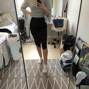 en svart högmidjad knälång kostymkjol, i bra skick, den har en liten slits i mitten, kan sänka priset vid snabb affär, fraktar men köparen får stå för fraktkostnaden, hör gärna av er om ni har frågor eller vill ha fler bilder :)
