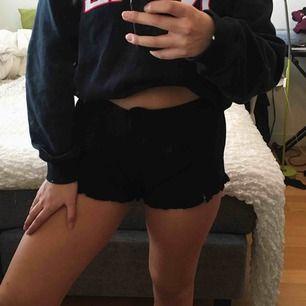 Svarta shorts med en liten volang i kanten, köpt på Bikbok. Perfekta i sommar när du vill vara snygg och bekväm!  Köparen står för frakt.