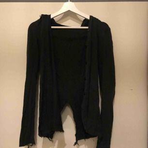 Fin svart, lite tuff tröja med luva och slitningar på kanterna. Går att knäppas med knappar. Sällan använd. Det står att tröjan är i stolek L, men det är den inte, den passar till XS-S.