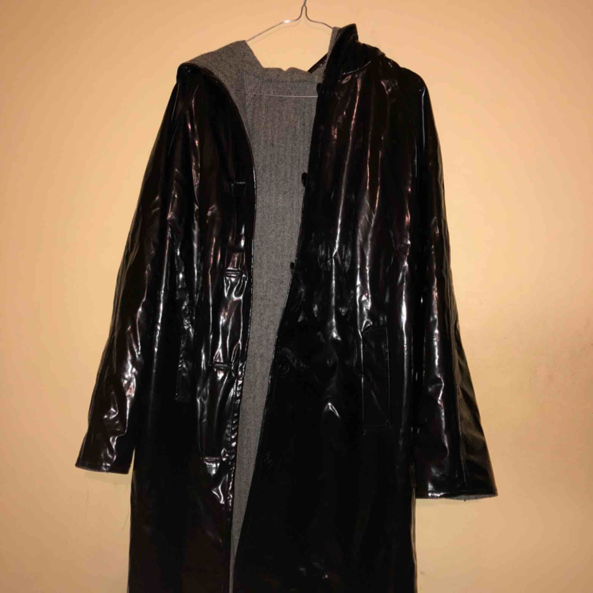 Vintage double sided coat. One side is shiny black faux leather. The other a herringbone coat pattern. Both wet and dry cold weather. Both sides have buttons and pockets. Has a very large hood.. Jackor.
