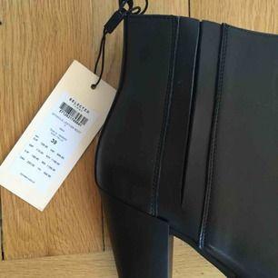 Snygga nya och helt oanvända äkta läder stövletter från Selected Femme med klack i bekväm höjd.  Butikspris 1,200kr!  Storlek 39 (passar även 38)  Snygg detalj med gömt resår på sidan - bara att dra på!  Har Swish. Kan skickas. Rökfritt & Djurfritt hem.