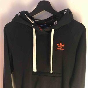 en fin mörkblå hoodie med orange adidas märke på ryggen🦋 har även en magficka. knappt använd