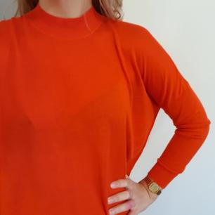 Jääättefin tunn tröja från Monki i en riktigt klarröd färg. Slits på sidorna.