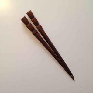 Två hårpinnar i brunt trä.