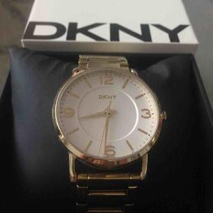 Enkel och stilren guldklocka från DKNY. Använd och i bra skick, men med några repor på uret samt på armbandet. Länk till armbandet för att göra den större finns.   Köparen betalar frakt annars kan köp göras i Göteborg.