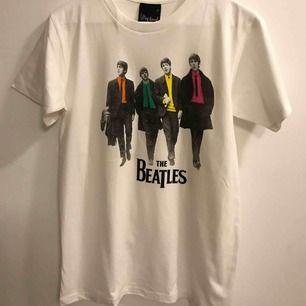 The Beatles Walking Down The Street t-shirt, stl Large. Från axel ner är den ca 69cm och på bredden från armhåla till armhåla är den ca 48cm. Den är ny och aldrig använd. Hämtas upp i Enskededalen eller skickas mot 18:- Har ca 10st kvar av denna.
