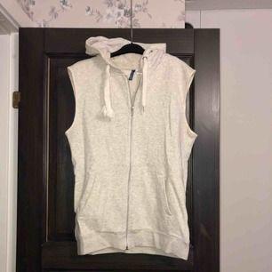 Grå hoodie-väst i nyskick. Aldrig använd, endast provad. Köparen betalar frakten (ca 45kr) eller hämtar upp kläderna i Skärholmen (Bredäng). Kan även mötas upp i Skärholmen.