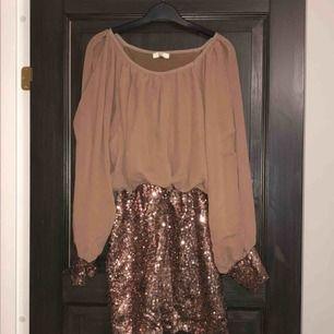 Paljettklänning brun/bronsfärgad i nyskick. Aldrig använd, endast provad. Köparen betalar frakten (ca 45kr) eller hämtar upp kläderna i Skärholmen (Bredäng). Kan även mötas upp i Skärholmen.
