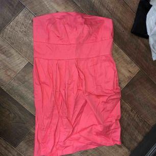 Rosa tubklänning i nyskick. Aldrig använd, endast provad. Köparen betalar frakten (ca 45kr) eller hämtar upp kläderna i Skärholmen (Bredäng). Kan även mötas upp i Skärholmen.