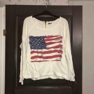 Vit tröja med usa-tryck i nyskick. Aldrig använd, endast provad. Köparen betalar frakten (ca 45kr) eller hämtar upp kläderna i Skärholmen (Bredäng). Kan även mötas upp i Skärholmen.